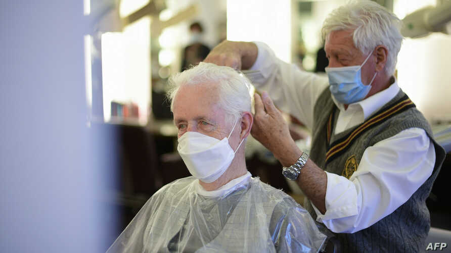 FILE - A barber wearing a face mask cuts the hair of a client, also masked, at his barber shop in Dortmund, Germany, May 4, 2020, amid signs of the coronavirus spread slowing in the country.