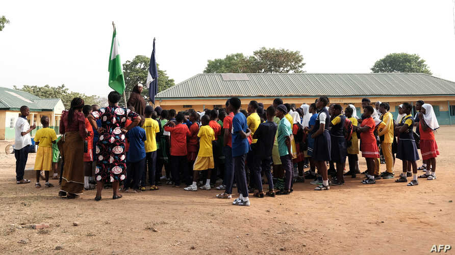 The principal of Government Secondary School, Tudun Wada, announcing the closure of schools to students at the assembly ground following an order by the Nigerian Government amid fears of the spreading of the COVID-19, in Abuja, March 20, 2020.