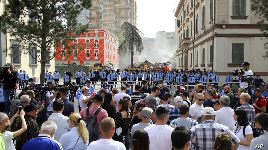 Police block rotesters during the demolition of the national theater building in Tirana, Albania, May 17, 2020.