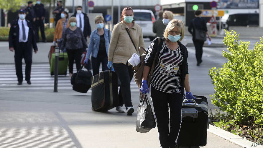 Romanian care workers with face masks accompanied by police and security arrive at the train station of Vienna's Schwechat airport, Austria, May 11, 2020.