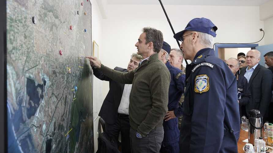 FILE - Greece's Prime Minister Kyriakos Mitsotakis points a map in the village of Feres, Evros region, at the Greek-Turkish border, March 3, 2020.