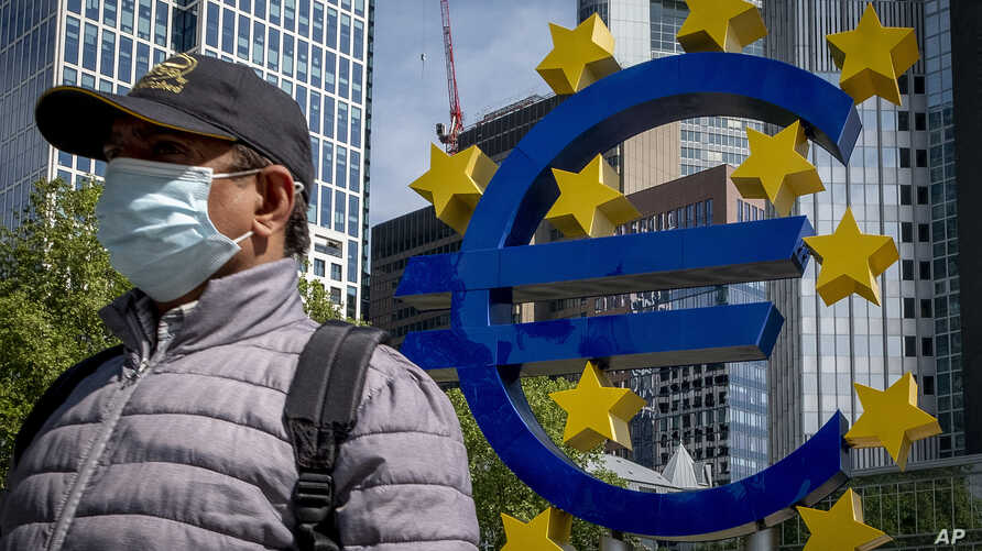 FILE - A man walks by an artistic representation of Europe's euro currency sign, in front of the old the European Central Bank in Frankfurt, Germany, May 5, 2020.