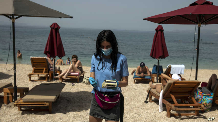 An employee of a beach bar, wearing a protective mask against the coronavirus, collects money for sunbeds, at Alimos beach, near Athens, Saturday, May 16, 2020.