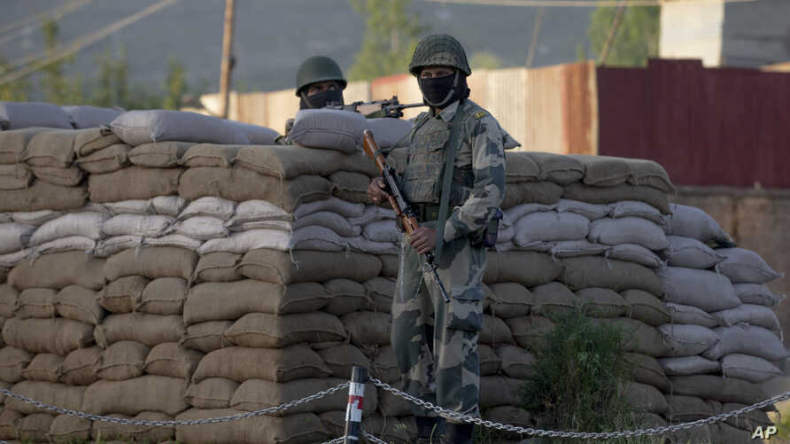 Border Security Force soldiers stand guard near the site of a shootout on the outskirts of Srinagar, Indian controlled Kashmir, May 20, 2020.