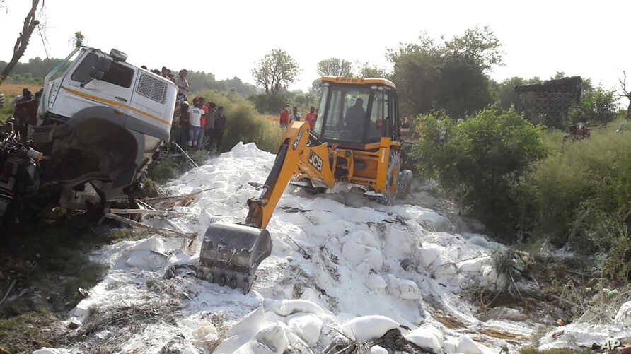 An excavator clears bags of white cement scattered on a road after a truck accident near Auraiya, a village in Uttar Pradesh state, India, May 16, 2020.