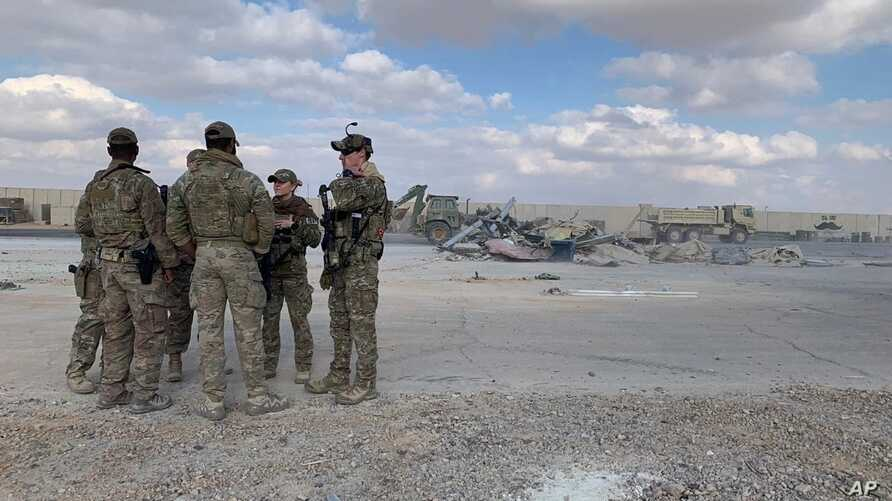 FILE - U.S. Soldiers stand while bulldozers clear rubble and debris at Ain al-Asad air base in Anbar, Iraq, Jan. 13, 2020.