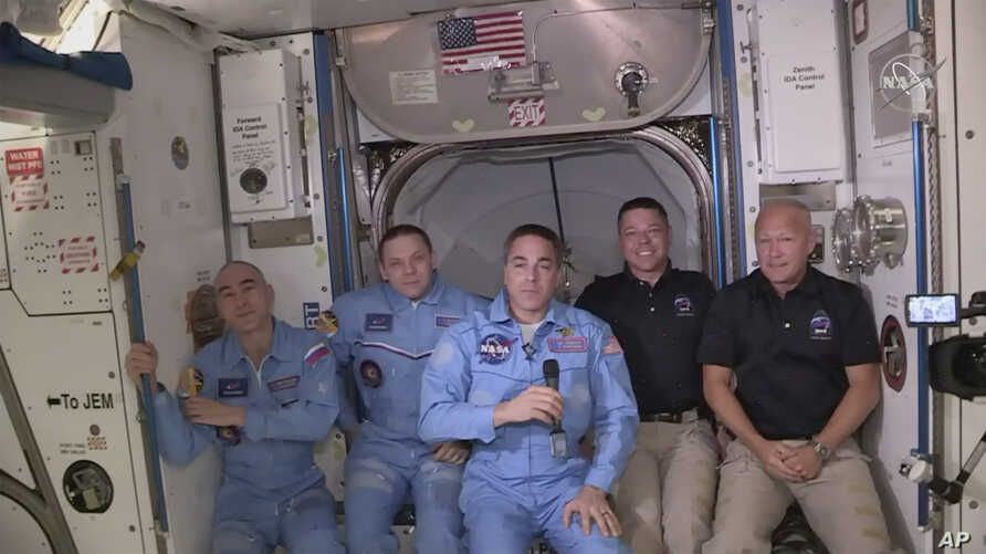 This photo provided NASA shows Bob Behnken and Doug Hurley, far right, joining the the crew at the International Space Station, after the SpaceX Dragon capsule pulled up to the station and docked May 31, 2020.