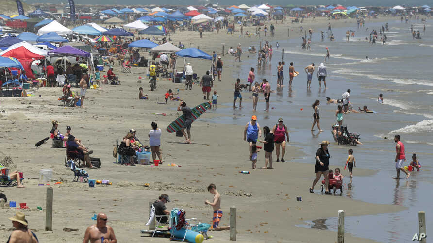 People gather on the beach for the Memorial Day weekend in Port Aransas, Texas, May 23, 2020. Beachgoers are being urged to practice social distancing to guard against COVID-19.
