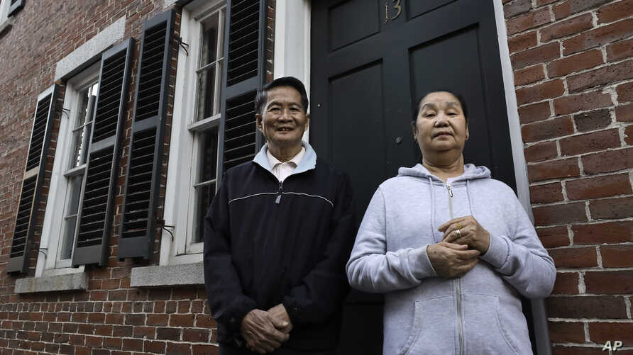 New U.S. citizens Pay Reh, left, and Poe Meh, originally from Myanmar, also known as Burma, stand for a photograph at the entrance to their home, in Lowell, Massachusetts, May 20, 2020. Both were among those granted a special oath ceremony last week.