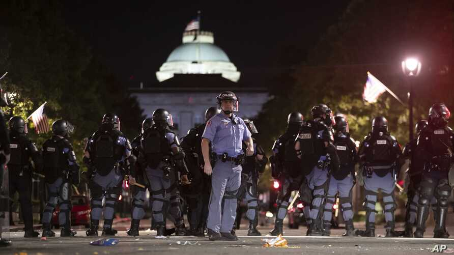 Raleigh Police block Fayetteville Street at Hargett Street as they work to return order after a night of violent demonstrations, May 31, 2020, in Raleigh, North Carolina.