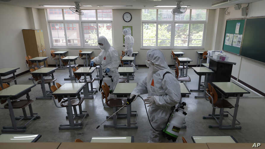 Health officials wearing protective gear spray disinfectant to help reduce the spread of the new coronavirus in a class at a high school in Seoul, South Korea, May 11, 2020.