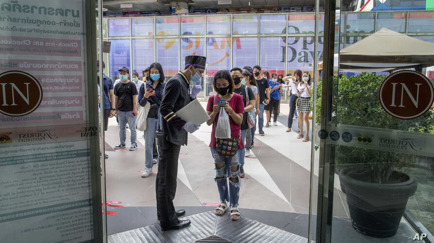 A woman displays her phone to doorman, to confirm using a mobile application to help contact-tracing at the entrance to the upmarket shopping mall Siam Paragon in Bangkok, Thailand, May 17, 2020.