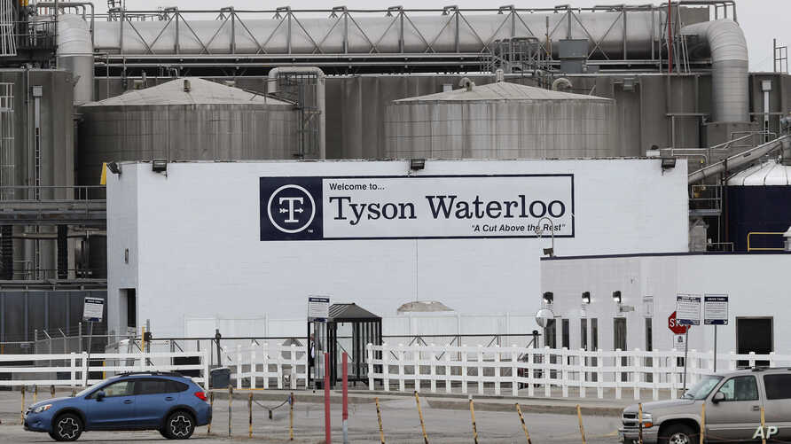 FILE - Vehicles sit in a near empty parking lot outside the Tyson Foods plant in Waterloo, Iowa, May 1, 2020.