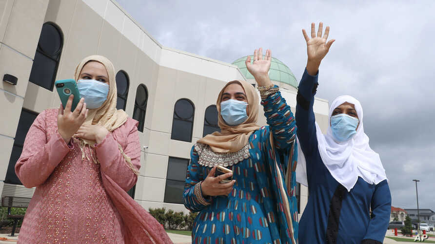 Saba Mahjabeen, right, and Gizman Mawi, center, waive as Sophia Baig looks on during a drive-through Eid al-Fitr celebration outside a closed mosque in Plano, Texas, May 24, 2020.
