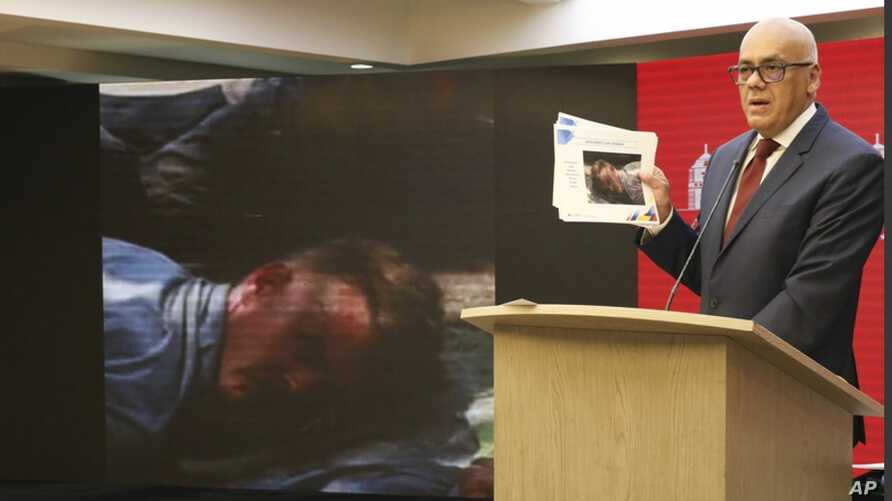 In this photo released by the Venezuelan Communications Ministry press office, Communications Minister Jorge Rodriguez shows a photograph of a man he identifies as former U.S. special forces soldier Luke Denman during his arrest, in Caracas, May 5, 2020.