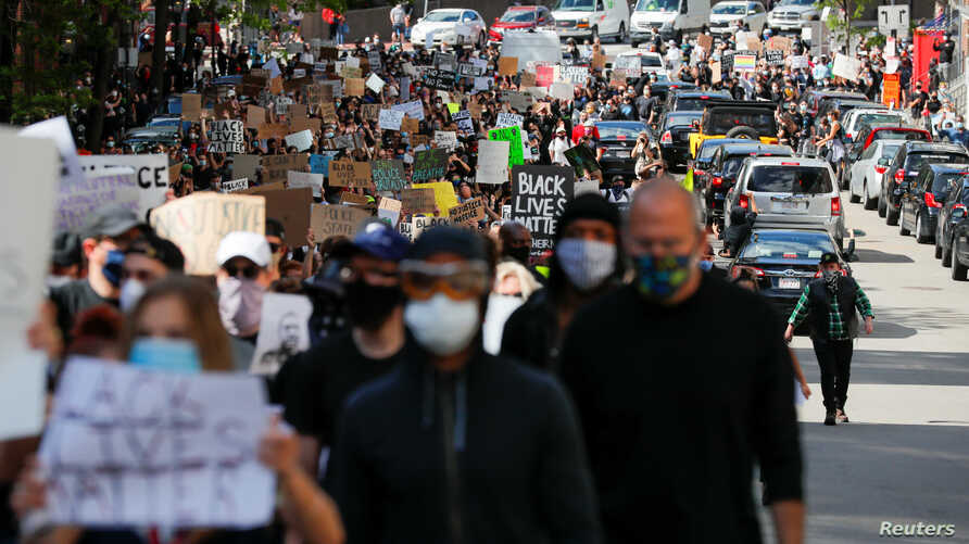 Protesters carry signs at a rally following the death in Minneapolis police custody of George Floyd, in Boston, Massachusetts, May 31, 2020.