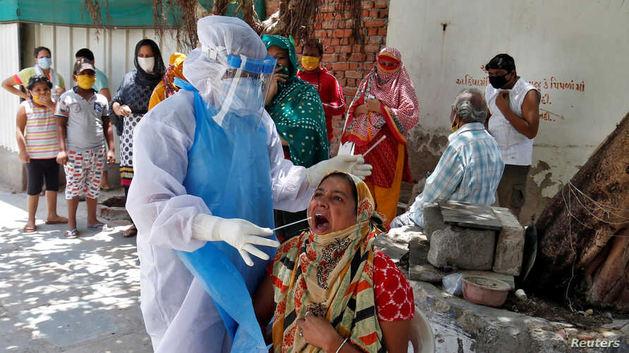 A woman reacts as a health care worker wearing protective gear takes a swab to test for the coronavirus, in a residential area, in Ahmedabad, India, May 22, 2020.