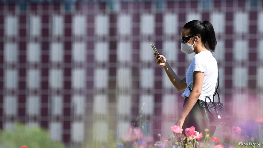 FILE - A young woman wearing a face mask to protect against the coronavirus checks her phone in a park in the Porta Nuova district, in Milan, Italy, May 4, 2020.