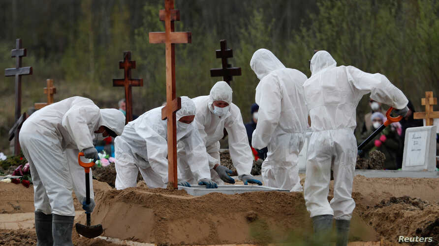 FILE - Grave diggers wearing protective gear bury a presumed victim of the coronavirus disease COVID-19, in a special section of a cemetery on the outskirts of Saint Petersburg, Russia, May 13, 2020.