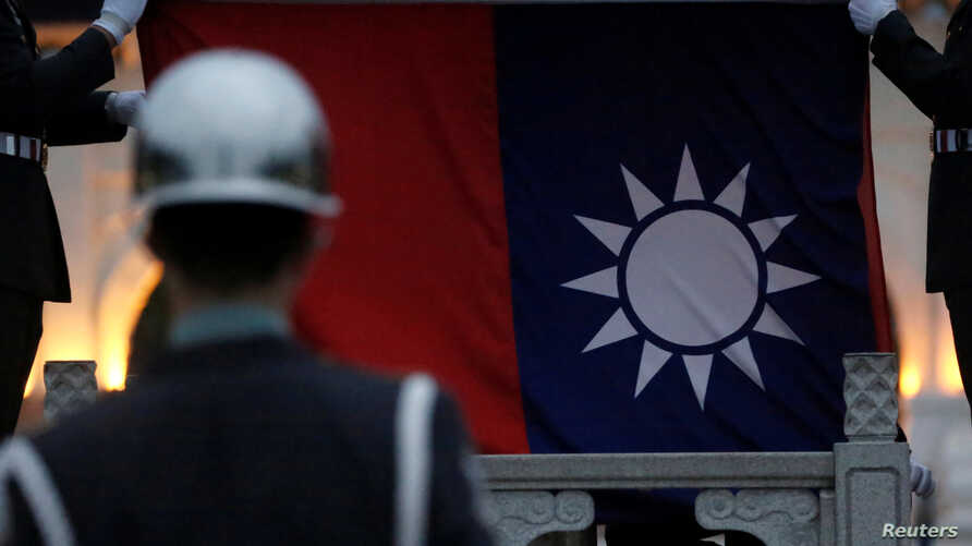 FILE - Honor guards lower a Taiwanese flag at Liberty Square, in Taipei, Taiwan, April 1, 2020.