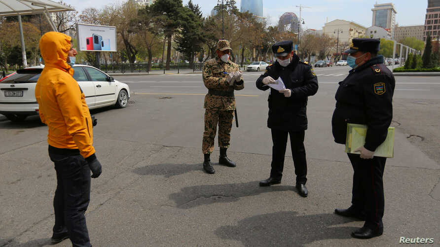 Azeri law enforcement officers and a serviceman check documents of a man after the authorities imposed restrictions on movement to prevent the spread of the coronavirus disease (COVID-19) in Baku, Azerbaijan, April 6, 2020.