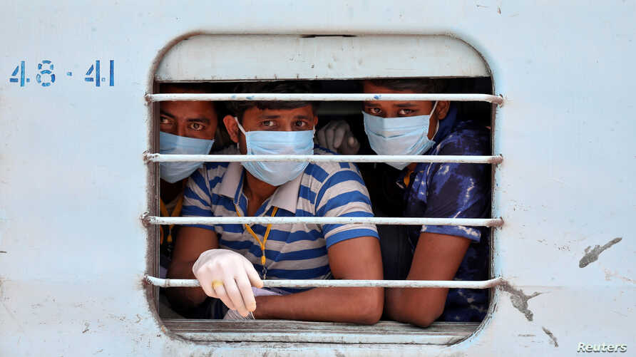 Migrant workers, who were stranded in the western state of Rajasthan due to a coronavirus lockdown, look out from a window of a train upon their arrival in their home state of eastern West Bengal, India.
