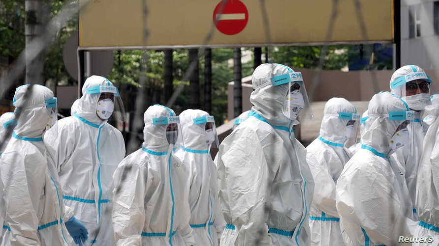Police officers wearing protective suits gather outside an apartment under enhanced lockdown to pick up illegal immigrants, due to the outbreak of the coronavirus disease (COVID-19), in Kuala Lumpur, Malaysia, May 1, 2020.