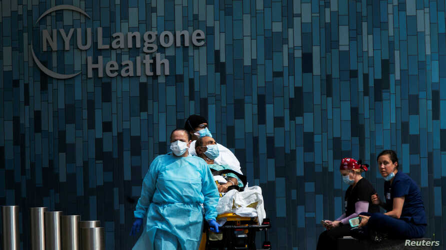 Health workers move a patient wearing a face mask at the at NYU Langone Hospital, during the outbreak of the coronavirus disease (COVID-19) in the Manhattan borough of New York City, New York, May 3, 2020.