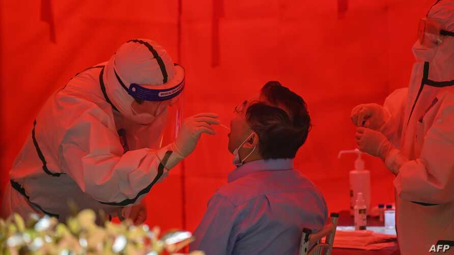 A medical worker takes a swab sample from a man to test for the COVID-19 coronavirus in Wuhan, in China's central Hubei…