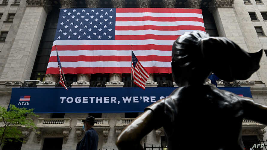 (FILES) In this file photo a man passes the building before the opening bell at the New York Stock Exchange (NYSE) on May 26,…