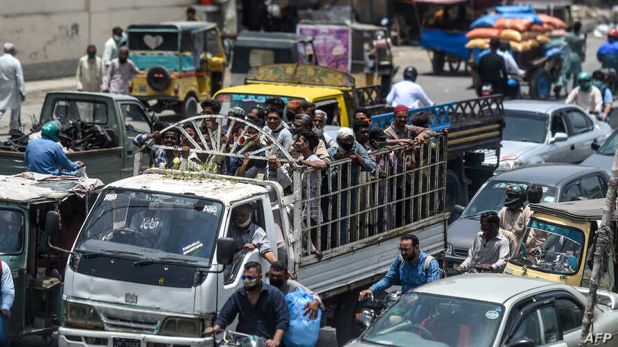 People ride on the back of a mini truck (C) after the government resumed public transport services easing the lockdown imposed…