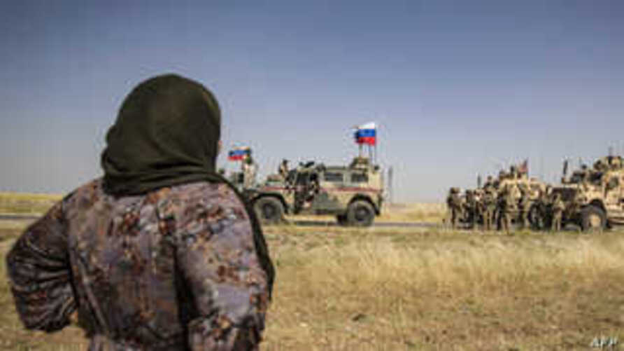 A Syrian woman looks at US and Russian soldiers in the northeastern Syrian town of al-Malikiyah (Derik) at the border with…
