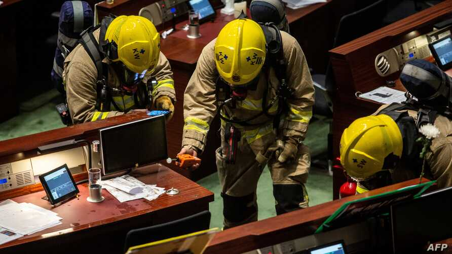 Members of the fire brigade perform tests in the main chamber of the Legislative Council after pan-democrat lawmakers hurled an…
