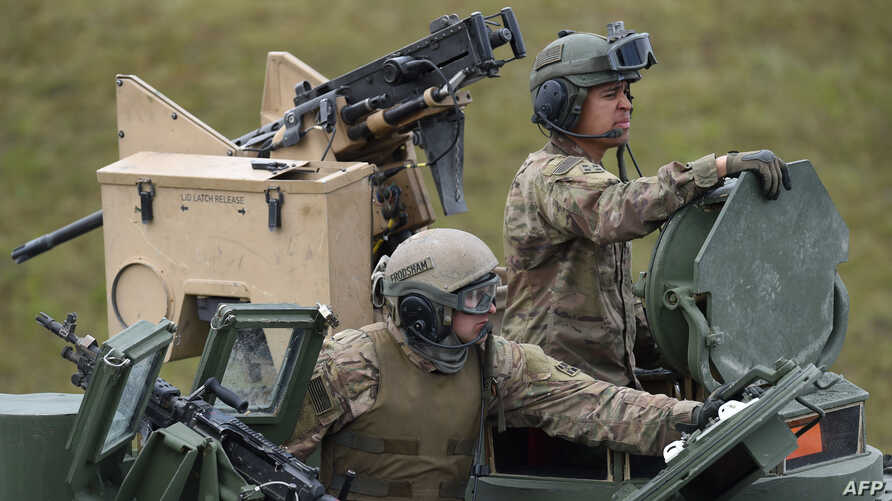 (FILES) In this file photo taken on May 12, 2017, US soldiers sit in a tank type 'M1A2 SEP'  during the exercise 'Strong Europe…