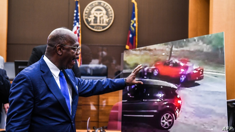 Fulton County District Attorney Paul Howard shows a picture of the incident in a courtroom as he announces 11 charges against…