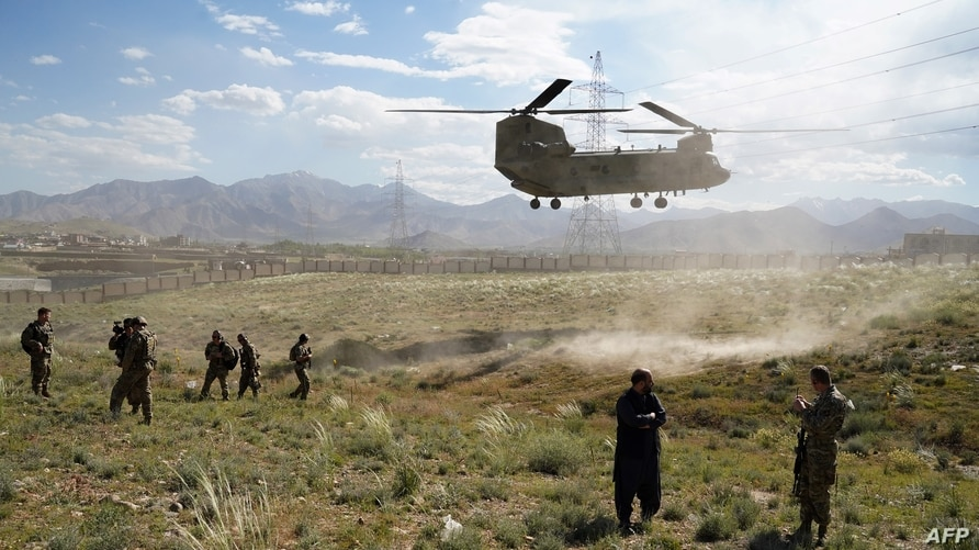 In this file photo taken on June 6, 2019 a U.S. military Chinook helicopter lands on a field during a visit by the Gen. Scott Miller, commander of US and NATO forces in Afghanistan.
