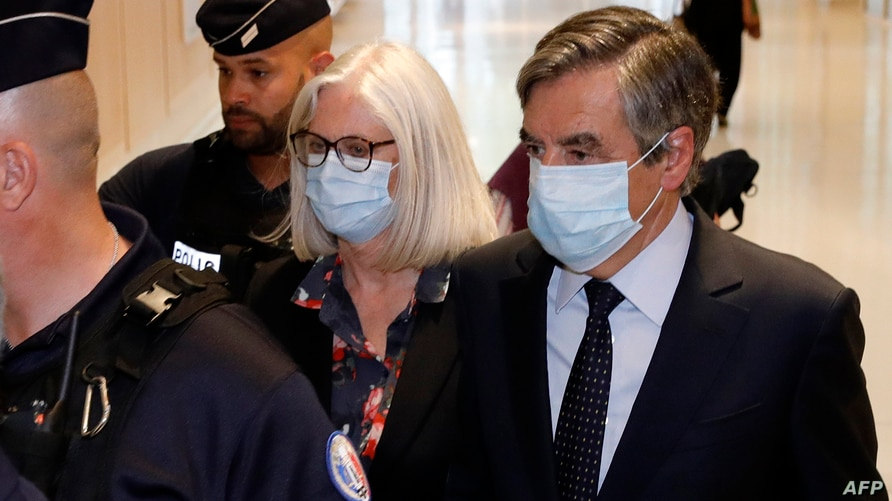 Former French Prime minister Francois Fillon (R) and his wife Penelope Fillon (2nd-R) leave the Paris' courthouse on June 29,…
