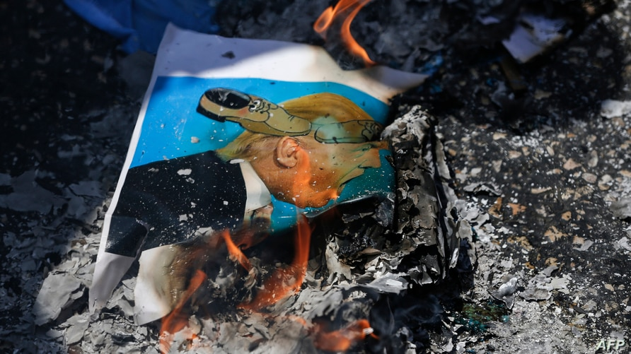 A picture taken on August 24, 2017 in the West Bank city of Ramallah shows the remains of a burnt flyer depicting US President…