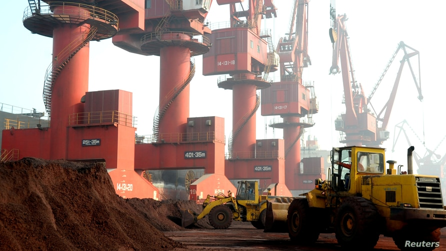 FILE - Workers transport soil containing rare earth elements for export at a port in Lianyungang, Jiangsu province, China…