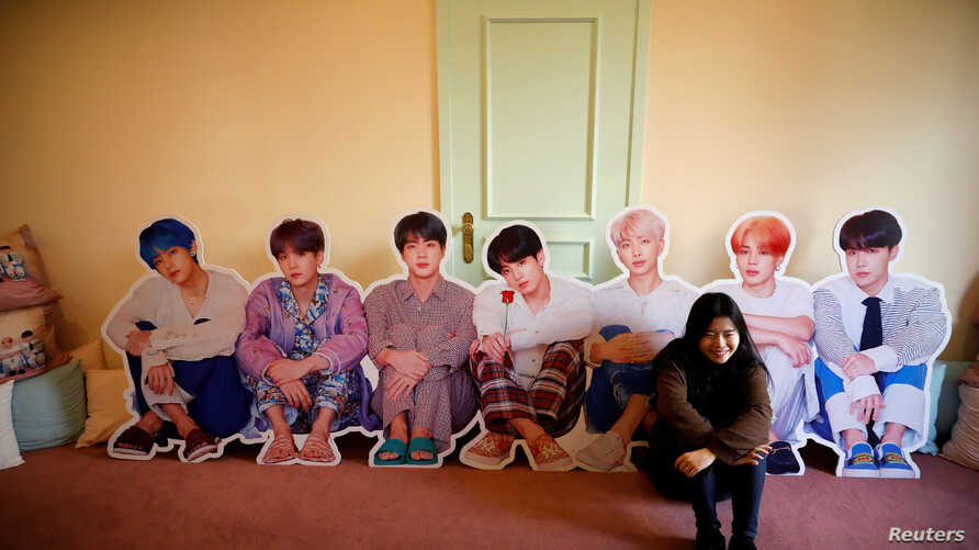A fan of K-pop idol boy band BTS poses for photographs with cut-out of BTS