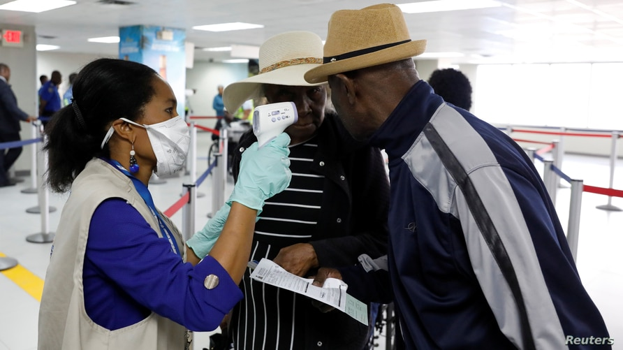 Travellers arriving in Haiti at the International Airport Toussaint Louverture get their temperature checked