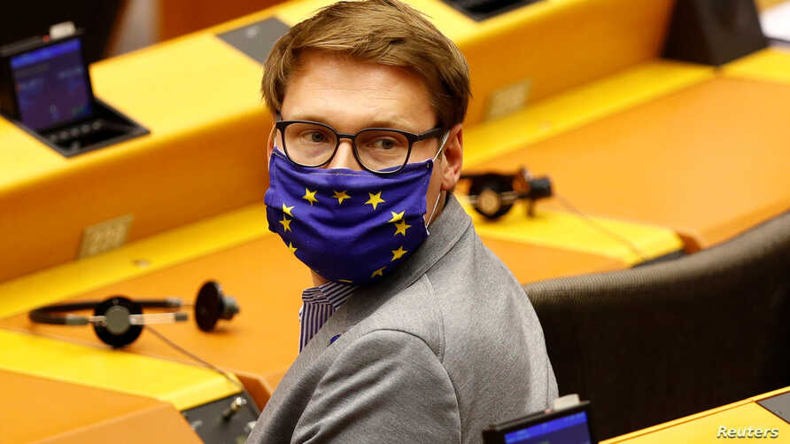 Member of the European Parliament Moritz Korner, wearing a protective face mask with the EU flag, is seen during a plenary…