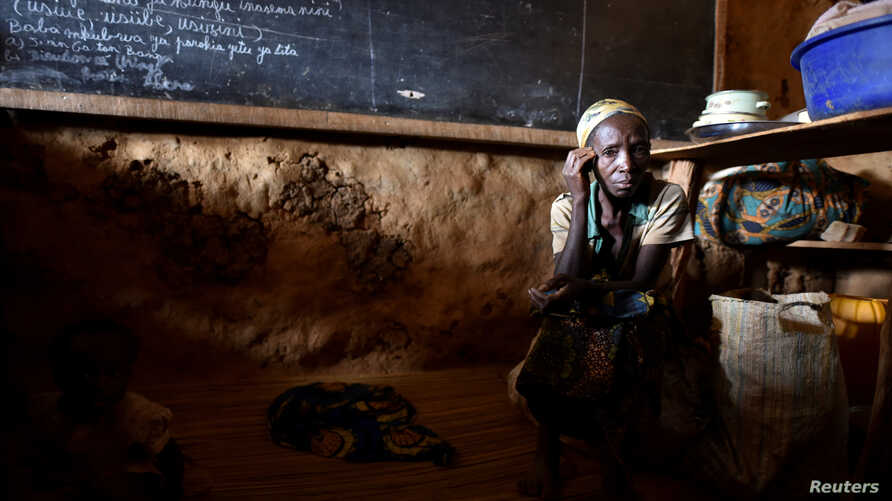 FILE PHOTO: An internally displaced Congolese woman and her child sit inside a classroom used by victims of ethnic violence in…