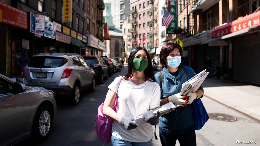 Shirley Ng (l) , a volunteer with the Chinatown Block Watch neighborhood patrol group, distributes Chinese newspaper along a…
