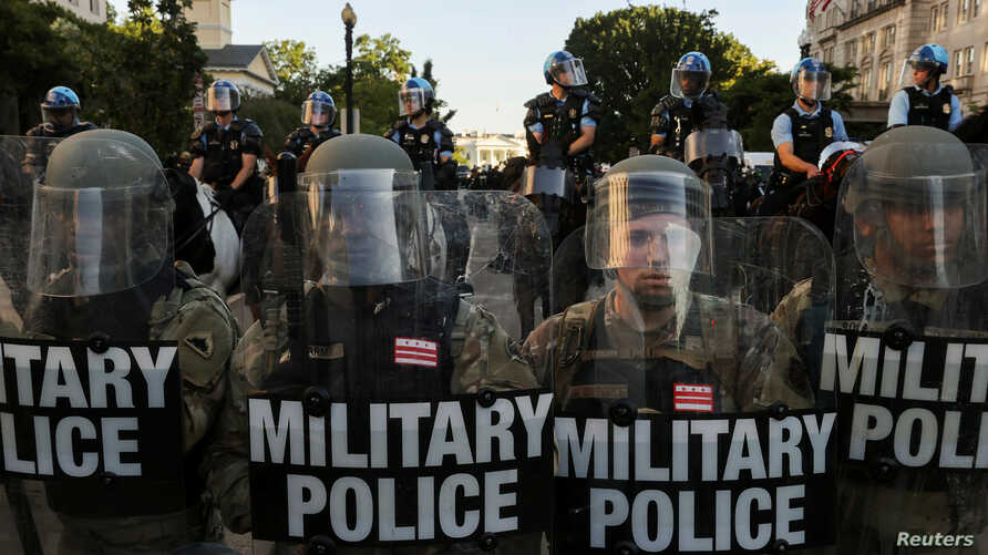 FILE PHOTO: DC National Guard Military Police officers and law enforcement officers stand guard during a protests against the…