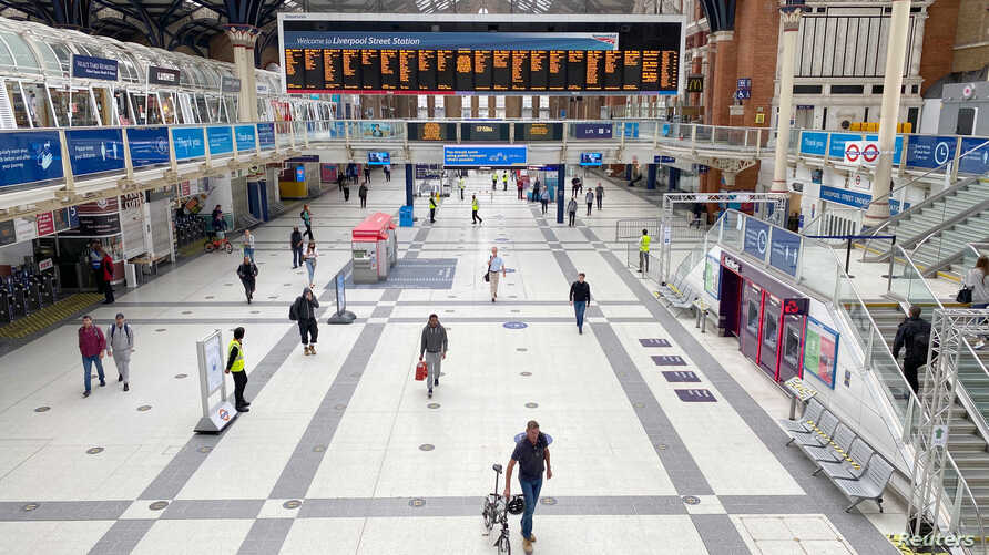 A man pushes his bicycle across the concourse of Liverpool Street railway station during morning rush hour, following the…
