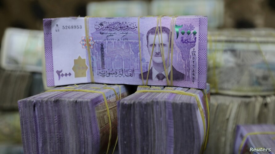 FILE PHOTO: Syrian pounds are pictured inside an exchange currency shop in Azaz, Syria February 3, 2020. Picture taken February…