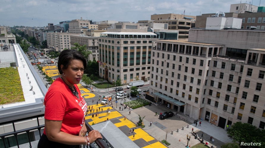 Mayor Muriel Bowser looks out over a Black Lives Matter sign that was painted on a street, during nationwide protests against…