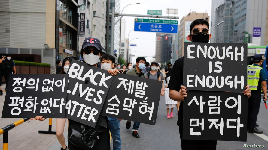 People march on the street in solidarity with protests against the death in Minneapolis police custody of George Floyd in Seoul…