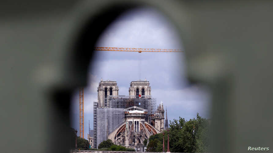 A view shows Notre Dame Cathedral, as workers prepare to remove damaged scaffolding elements from the remains of the burnt roof…